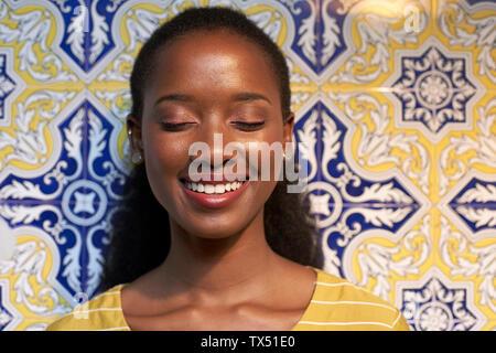 Ritratto di un felice giovane donna in corrispondenza di una parete piastrellata