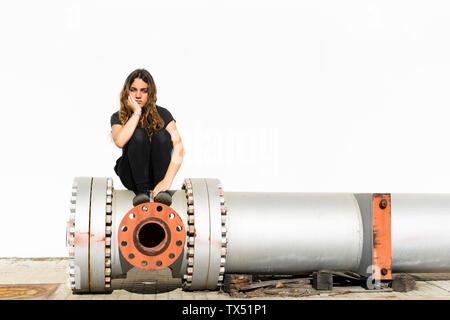 Ritratto di grave ragazza seduta sul tubo di grandi dimensioni
