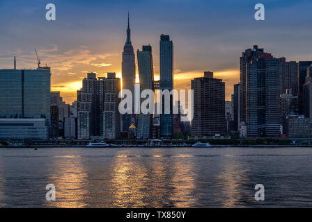 La Skyline di Manhattan e Empire State Building attraverso la East River al tramonto, Manhattan, New York, Stati Uniti d'America
