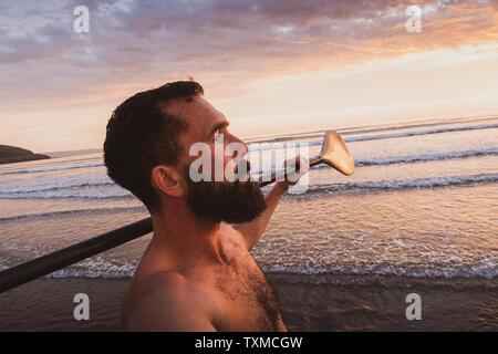 Un barbuto uomo cammina verso il mare con uno Stand Up Paddle board e la pala al tramonto sulla spiaggia nel Devon Regno Unito