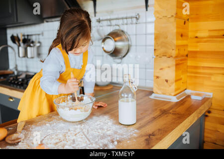 Un po' carina ragazza ottenere pronto per cuocere una torta in cucina. Agitazione l'impasto in una ciotola. La farina e il latte sulla tavola. Foto Stock