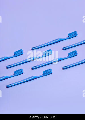 Gli spazzolini da denti disposti in ranghi su sfondo lilla