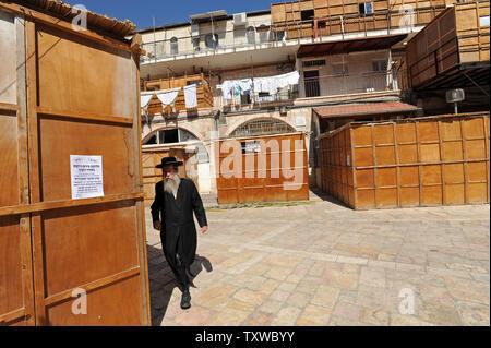 Un Ebreo Ultra-Orthodox uomo cammina passato una Sukkah in legno, la cabina di verniciatura tradizionale che è utilizzato durante la celebrazione di Sukkot,la Festa dei Tabernacoli, in Mea Shearim a Gerusalemme, 10 ottobre 2011. Sukkot la festa comincia il 13 ottobre e commemora l'esodo degli Ebrei dall Egitto. UPI/Debbie Hill