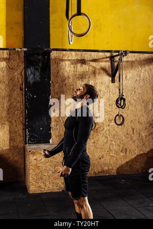 Montare il giovane uomo in nero sportwear esercitando con anelli di ginnastica in palestra Foto Stock