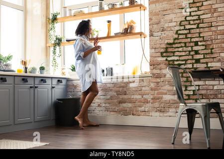 Donna incinta guardando fuori della sua finestra della cucina. Foto Stock