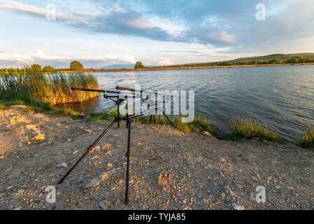 Le avventure di pesca, la pesca alla carpa. È la pesca con carpfishing tecnica. Campeggio in riva al lago. Foto Stock