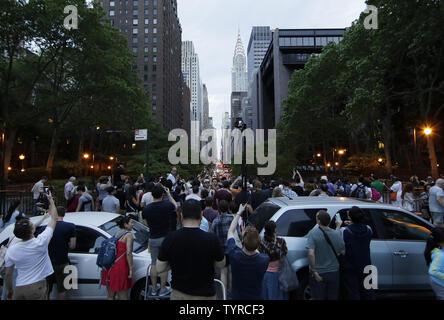 Le persone si radunano e scattare foto con una vista della 42nd Street a Manhattan con la speranza di vedere un evento Manhattanhenge che non potrebbero mai essere visualizzato a causa di nuvole pesanti nella città di New York il 29 maggio 2016. Il Manhattanhenge tramonto arriva due volte l'anno quando il sole al tramonto si allinea proprio con la Manhattan's street griglia. Foto di Giovanni Angelillo/UPI Foto Stock