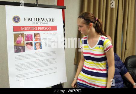 Hannah Jones (13) passeggiate passato una allargata persona mancante poster di sua madre Amanda Jones, a seguito di una conferenza stampa presso il San Luigi sede del Beureau federale di inchiesta in San Luigi il 5 agosto 2014. Amanda Jones è andato mancante, 8 1/2 mesi di gravidanza da Hillsboro, Missouri il 14 agosto 2005 e l'FBI, offrendo un $20.000 ricompensa, crede che ha nuovi lead in caso. UPI/Bill Greenblatt Foto Stock