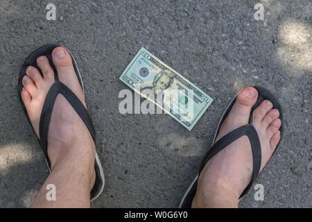 Il denaro si trova sul marciapiede sotto i piedi di un giovane uomo in flip-flop Foto Stock