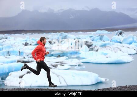 Uomo che corre. In volata trail runner in fast sprint nella bellissima natura. Montare atleta maschio sprinter cross country in esecuzione da Iceberg di Jokulsarlon lago glaciale in Islanda.