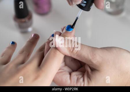 Una madre dipinge la sua ragazza giovane con le mani blu e rosa nailpolish, visto contro un isolato sfondo bianco Foto Stock