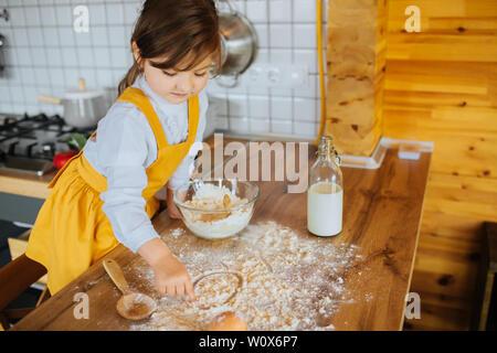 Una bambina aiutando la madre per cuocere al forno in cucina. Dito nella farina, disegno sulla superficie del tavolo. Foto Stock
