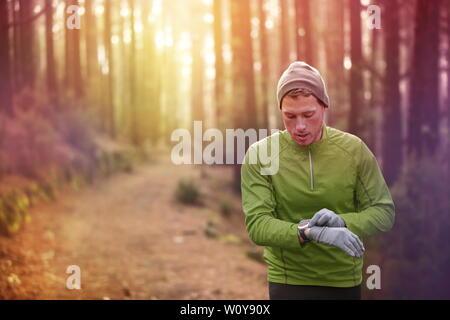 Trail Running runner guardando il monitor per la frequenza cardiaca guardare in esecuzione nella foresta di indossare una giacca calda sportswear, cappello e guanti. Pareggiatore maschio esegue la formazione nel bosco.