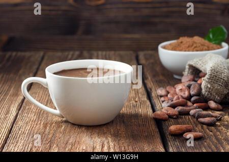 Bevanda di cacao in tazza bianca, il cacao in polvere e le fave di cacao su un tavolo di legno. Foto Stock