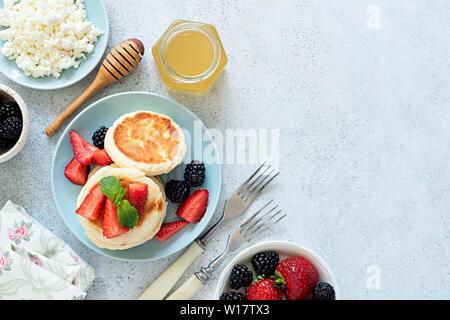 Syrniki cottage, frittelle di formaggio con frutti di bosco e miele. Tabella vista superiore, copia dello spazio. Una gustosa colazione sana e ricca in calcio e proteina