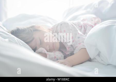 Asian bambina dormire nel letto la mattina tempo con sunrise luce soft focus sweet dream concept Foto Stock
