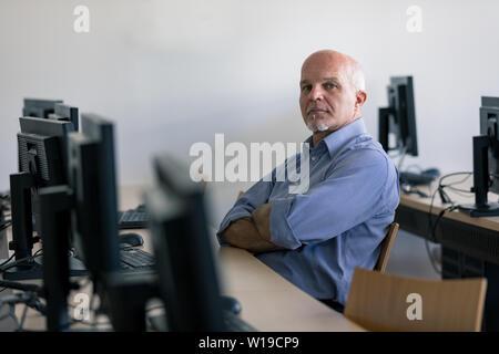 Riflessivo senior uomo seduto in un internet café con le braccia incrociate, computer in primo piano.