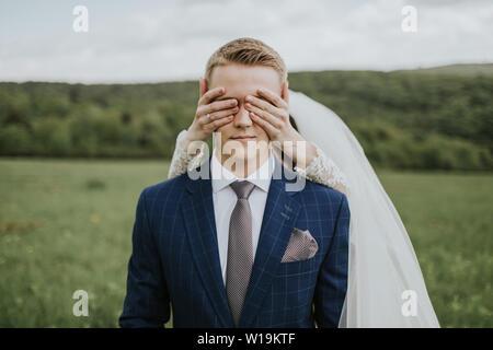 Sposa che copre gli occhi dello sposo. Ritratto di giovane sposo in attesa sul prato e sposa dietro di lui che copre la sua gli occhi. Foto Stock