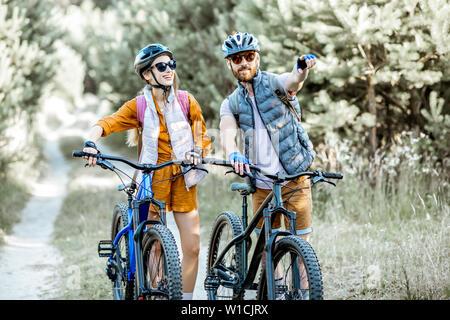 Coppia giovane Viaggiare con bici di montagna nella foresta, l uomo che mostra con la mano sul modo in avanti Foto Stock
