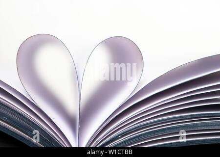 Pagine di un libro aperto a forma di cuore isolato su sfondo bianco. Amore per la lettura, il concetto di scienza, di apprendimento, di romanticismo