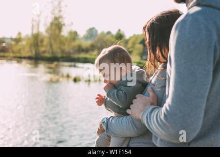 La famiglia felice con simpatici baby boy sul lago di fondo di acqua all'aperto, sensibilità al concetto di natura Foto Stock
