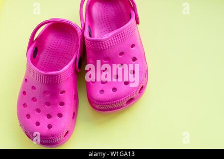 San Diego, Stati Uniti d'America,10 Maggio 2019.Estate rosa flip flop isolato su sfondo giallo. Bambini in gomma morbida o sandali Crocs.vacanze estive Scarpe alla moda Foto Stock