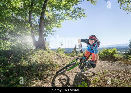 Mountain biker di equitazione in foresta, Baviera, Germania Foto Stock