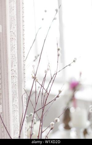 Vintage interno con uno specchio antico e un tavolo con un vaso e salici. Soft focus. Foto Stock