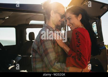 Coppia romantica abbracciando accanto alla loro vettura durante un viaggio su strada. Amare giovane uomo e donna con un grande tempo sul loro viaggio su strada. Foto Stock