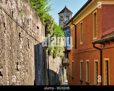 Strada desolata con via e pareti di pietra sull'Isola di San Giulio nel Lago d'Orta con il campanile di San Giulio Basilica in background durante una