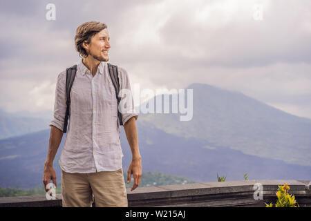 Outdoor Ritratto di giovane uomo che guarda sul vulcano Batur e Agung mountain view al mattino da Kintamani, Bali, Indonesia