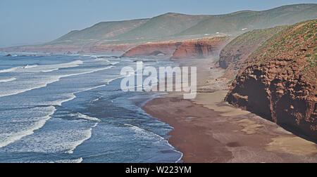 Red Rock con formazione di arco sulla spiaggia, Plage Sidi Ifni, Marocco, Africa Foto Stock