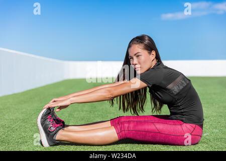Donna Fitness posteriori della coscia di stiramento dei muscoli delle gambe - tratto posteriore seduto con tocco dei piedi si allunga. Seduti piegare in avanti. Sport giovane atleta in activewear esercitare flessibilità sull'erba nella soleggiata palestra all'aperto. Foto Stock