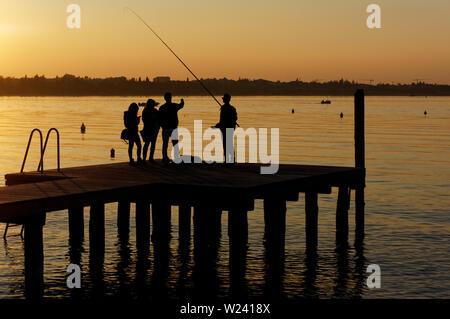 Un gruppo di giovani e di pesca parlando sul molo, irriconoscibile persone Foto Stock