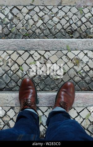 Le scarpe marrone sulla pavimentazione di pietra. Vista da sopra Foto Stock