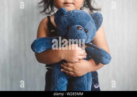 Piccola e dolce ragazza asiatica che abbraccia il suo giocattolo preferito Teddy bear. Concetto di bambino solitario, amore, infanzia e genitorialità. Messa a fuoco selettiva sul giocattolo di peluche. Foto Stock