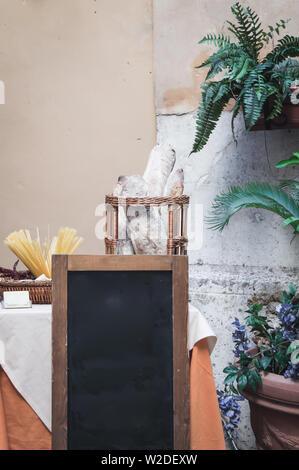 Vuoto in stile italiano vera lavagna nella parte anteriore della tavola con pasta e pane, circondato da piante