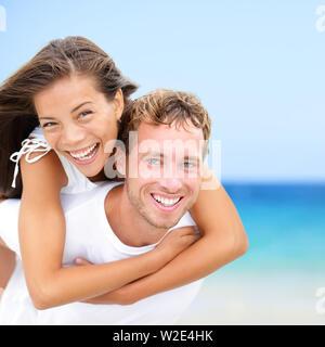 Coppia felice sulla spiaggia divertente vacanza estiva. Multirazziale giovane sposa giovane piggybacking sorridente gioioso euforico in felicità concetto sulla spiaggia tropicale con acqua blu, sky. Donna asiatica, uomo caucasico. Foto Stock