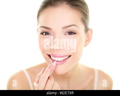 Il rossetto trucco donna mettendo balsamo per labbra cura. Bellezza ragazza asiatica applicare colore crema idratante sulle labbra pronte e guardando se stessa nello specchio sorridendo felice. Multi-etnico asiatico modello caucasico. Foto Stock
