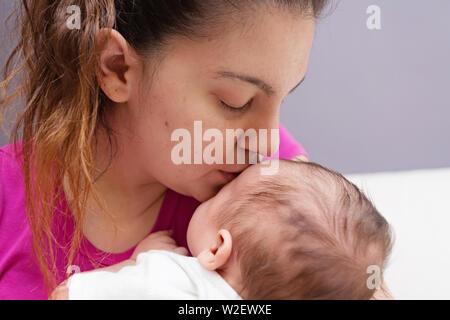 Amorevole snuggling Mom e baciare il suo nuovo di zecca baby Foto Stock