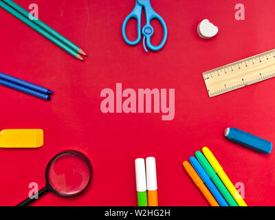Colorato di forniture scolastiche in disposizione circolare su sfondo rosso, torna al concetto di scuola. Foto Stock