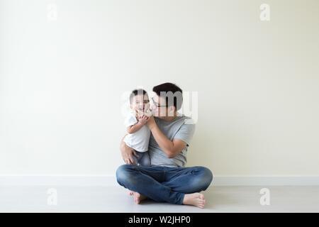 Asian padre e figlio giocando e sorridente sul pavimento in camera, Famiglia divertimento e risate concept Foto Stock