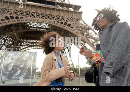 Giovane uomo e donna accanto alla Torre Eiffel a Parigi, Francia