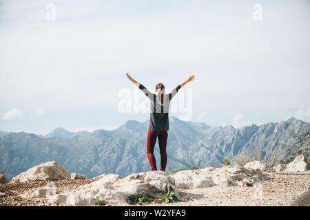 Ragazza sulla cima di una montagna o collina alza le mani verso l'alto. Lei è felice e libera.