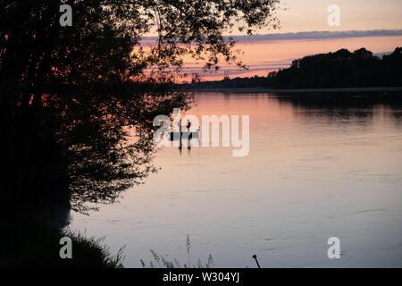 Barche di pescatori e la pesca in una tranquilla serata estiva al tramonto sul fiume Loira in Francia centrale