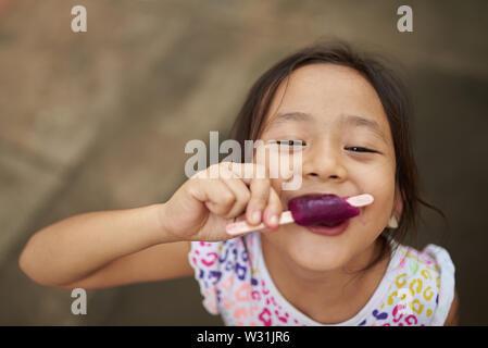 Ragazza asiatica a mangiare il gelato in all'aperto. Filipina kid mangiare un gelato e a fissare la fotocamera. Foto Stock