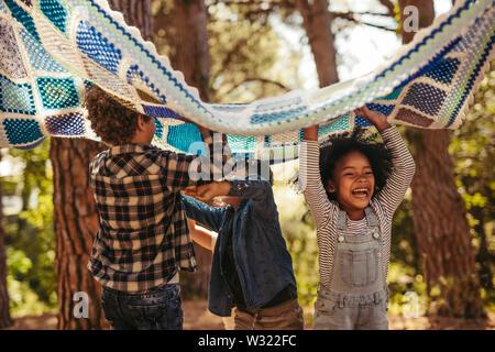 Quattro bambini nel parco con Coperta picnic. Gruppo di bambini godendo insieme nel parco. Foto Stock