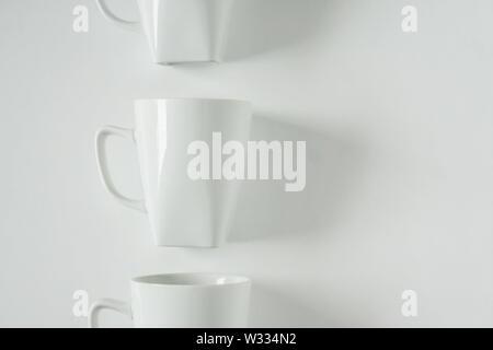 Uno singolarizzati monocromatici bianchi tazza da caffè allineate in una fila su sfondo bianco con vuoto camera vuoto lo spazio per testo, copia o copia di spazio. Moderno Foto Stock
