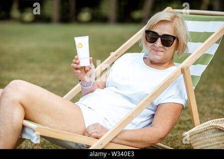 Ritratto di una donna senior con crema di protezione solare sdraiato sul lettino solare all'esterno. Concetto di protezione della pelle in età avanzata Foto Stock