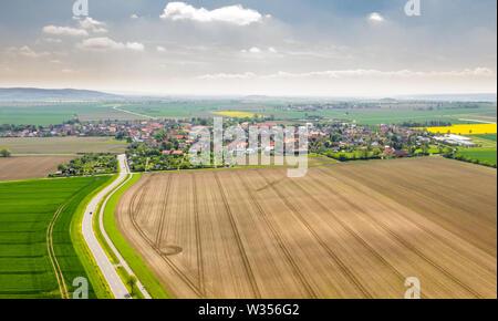Vista aerea di una strada tra i campi con un villaggio e un drammatico cielo con le nuvole in background.